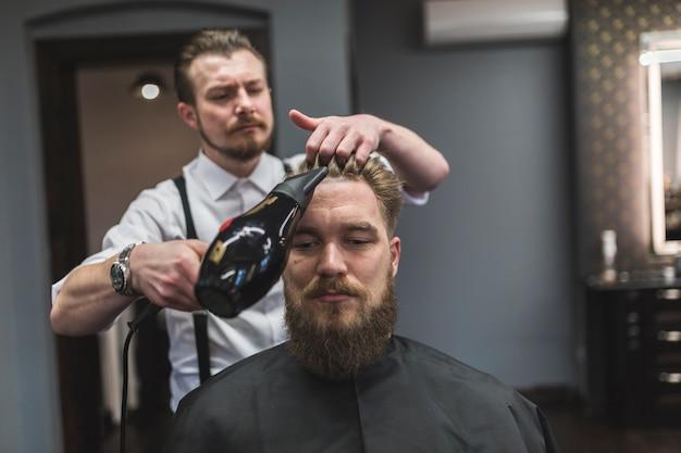 Peluquería secando el cabello del hombre barbudo