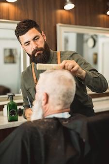 Peluquero adulto que corta el cabello de los clientes en la barbería.
