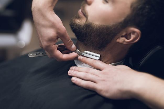 Peluquero se afeita la cabeza, bigote y barba al hombre.