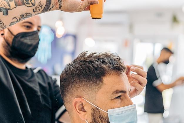 Peluquero arrojando polvos de talco en el cabello de un hombre caucásico con una máscara en una barbería