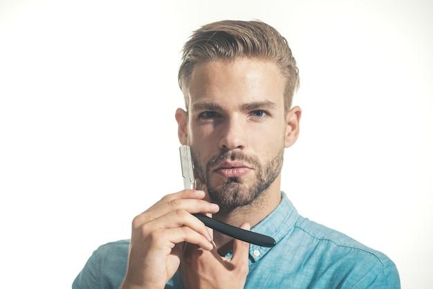Peluquero atractivo con barba negra y bigote sosteniendo una navaja de afeitar cerca de su peluquero de barba
