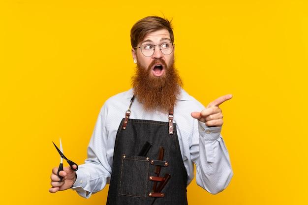 Peluquero con barba larga en un delantal amarillo sorprendido y apuntando con el dedo a un lado