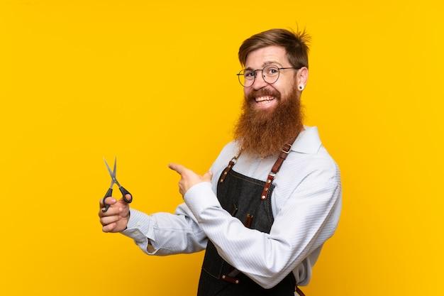 Peluquero con barba larga en un delantal sobre fondo amarillo aislado y apuntando