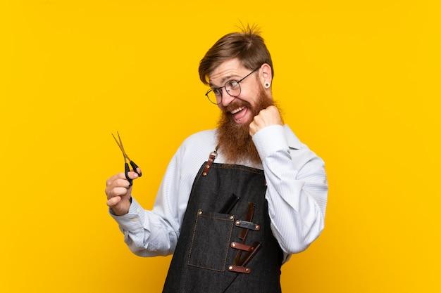 Peluquero con barba larga en un delantal sobre fondo amarillo aislado celebrando una victoria