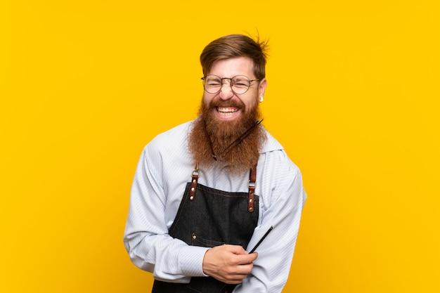 Peluquero con barba larga en un delantal sobre fondo amarillo aislado
