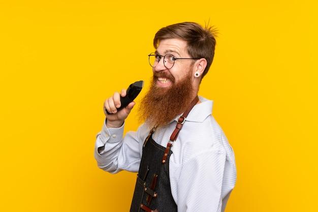 Peluquero con barba larga en un delantal sobre pared amarilla aislada