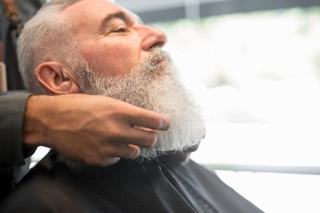 Peluquero corrigiendo barba a cliente anciano.