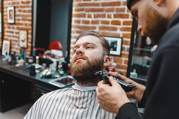 Peluquero cortando la barba a un cliente