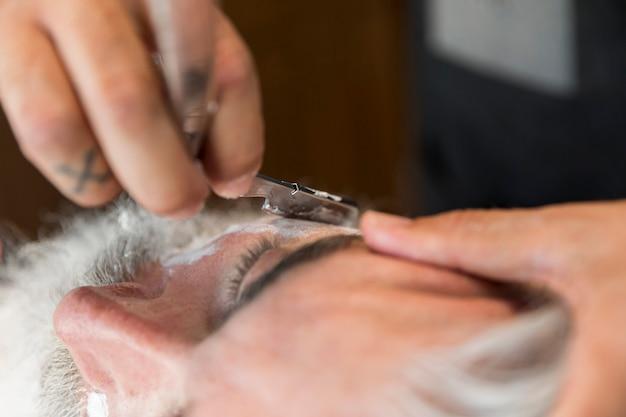 Peluquero cortando barba con navaja para cliente.