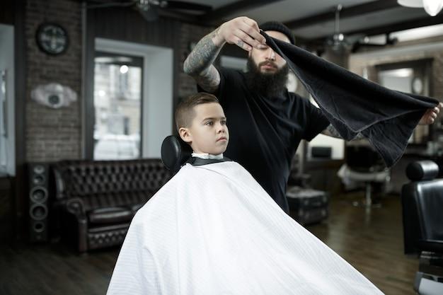 Peluquero cortando el cabello del niño
