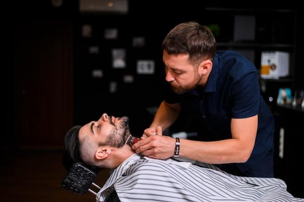 Peluquero de costado cortando la barba del cliente