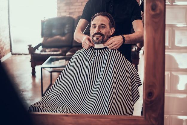 El peluquero está grabando a clientes en barbería