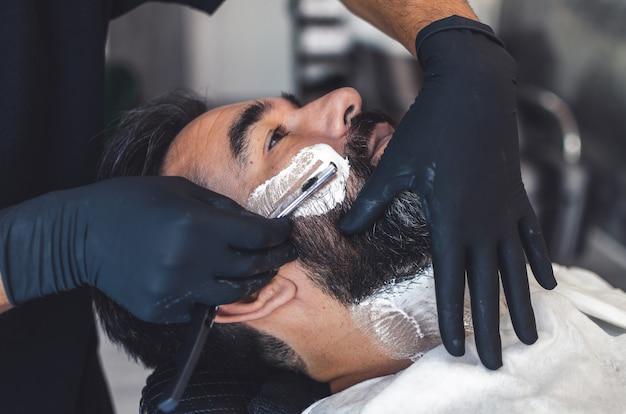 Peluquero en guantes de látex afeitando a un hombre guapo con un cuchillo