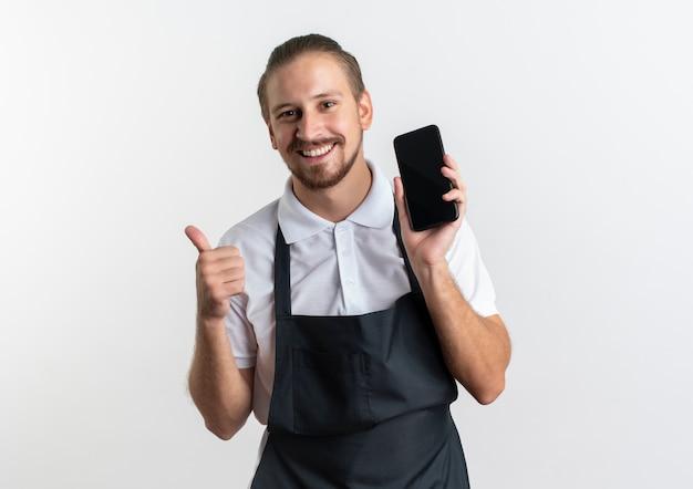 Peluquero guapo joven feliz vistiendo uniforme mostrando teléfono móvil y pulgar hacia arriba aislado en blanco con espacio de copia