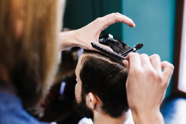 El peluquero hace el corte limpio antes de que el pelo del hombre del cuttin