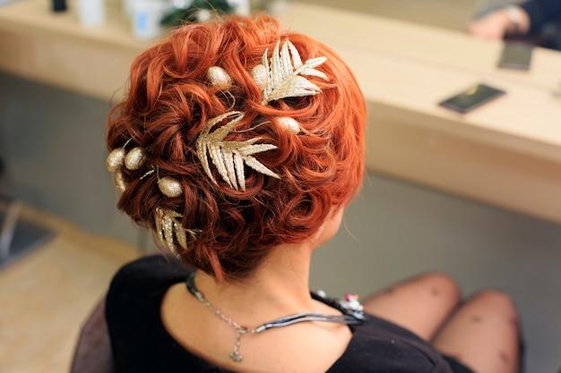 Peluquero hace hermoso peinado navideño en el salón