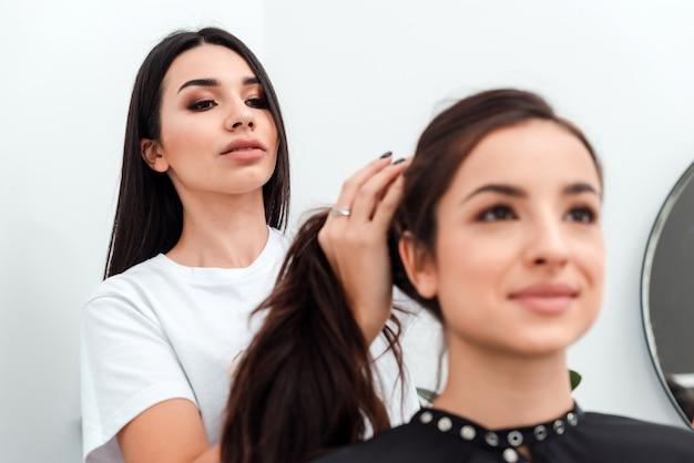 Peluquero hace peinado para mujer joven en salón de belleza
