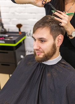 Peluquero haciendo corte de pelo para cliente masculino, hombre con barba con herramientas profesionales de peluquería