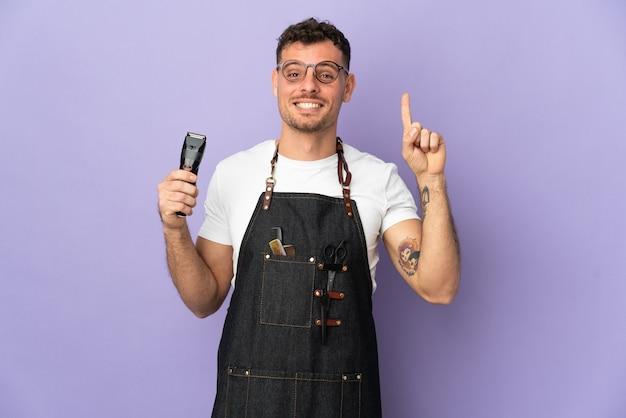 Peluquero hombre caucásico en un delantal aislado en la pared púrpura apuntando hacia una gran idea