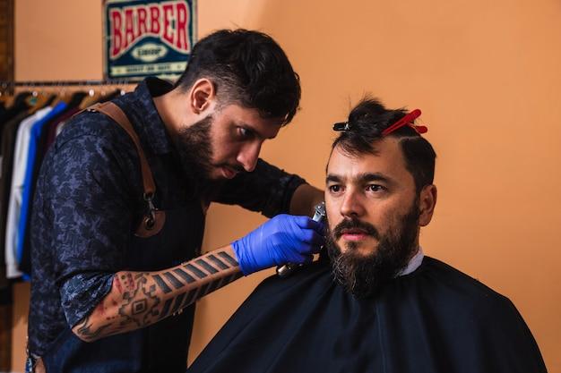 Peluquero latino recortando la barba del cliente