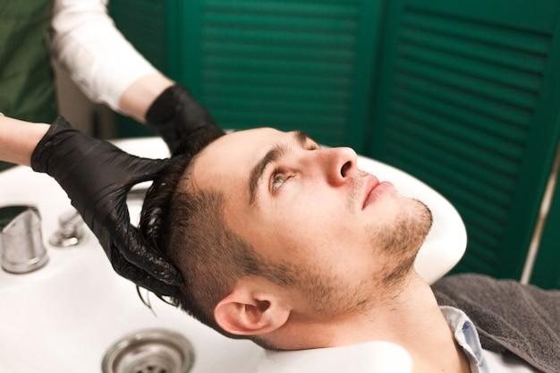El peluquero lava el cabello de un cliente antes de cortarlo. hombre guapo serio se lava la cabeza en un salón de belleza