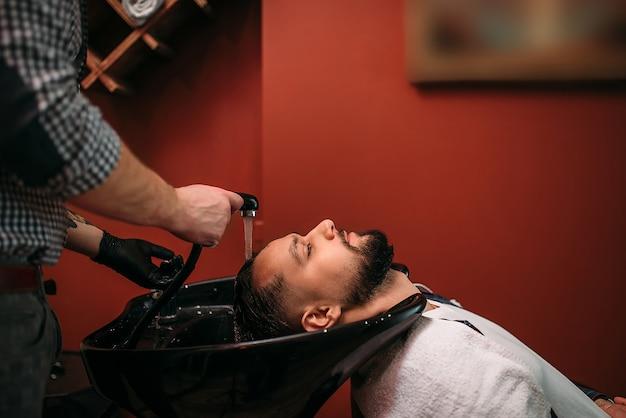 Peluquero lava el cabello de un cliente