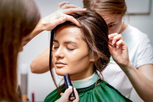El peluquero y el maquillador están haciendo peinado y maquillaje para una hermosa joven caucásica en un salón de belleza
