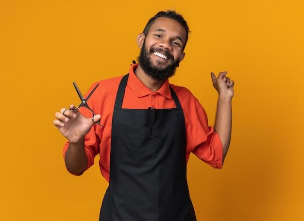 Peluquero masculino afroamericano joven alegre que lleva uniforme que sostiene las tijeras que apuntan detrás aislado en la pared anaranjada