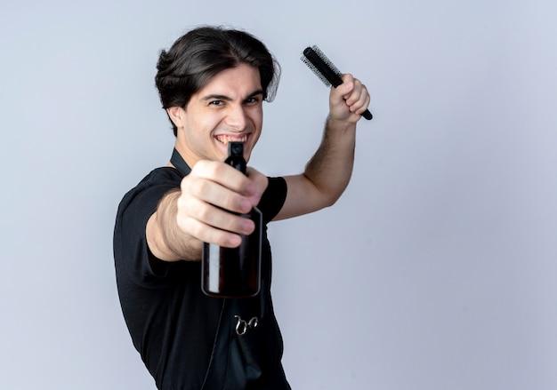 Peluquero masculino guapo joven alegre en uniforme sosteniendo la botella de spray en la cámara y levantando el peine aislado sobre fondo blanco