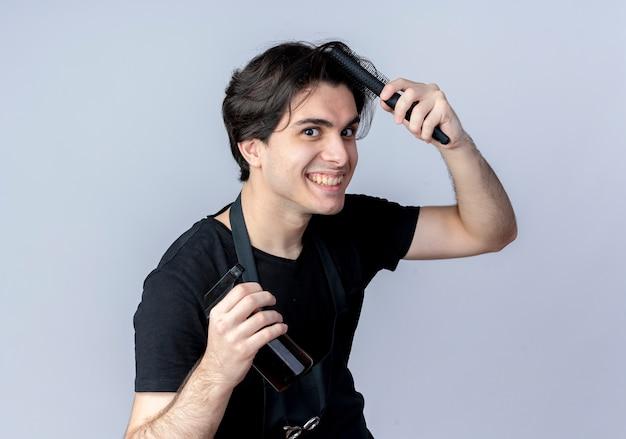 Peluquero masculino guapo joven sonriente en uniforme peinándose y sosteniendo una botella de spray aislado en blanco