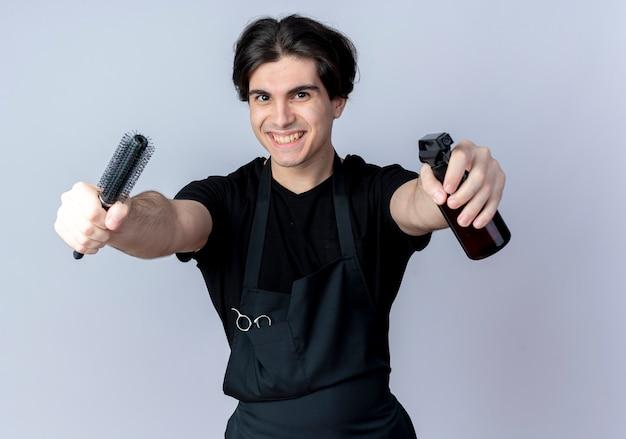 Peluquero masculino guapo joven sonriente en uniforme sosteniendo el peine con botella de spray en la cámara aislada en blanco