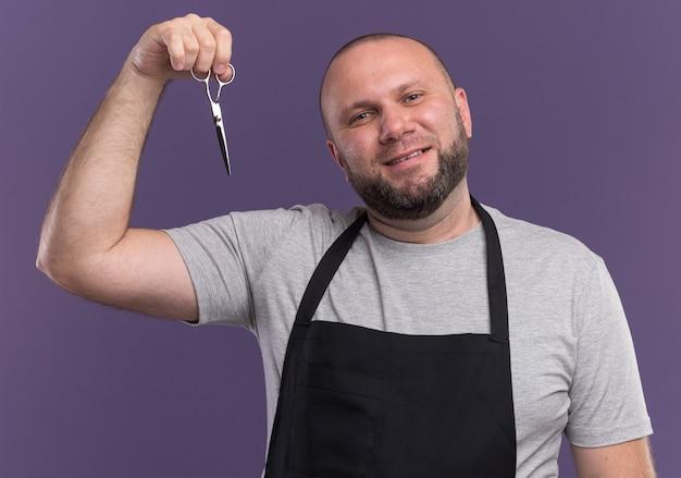 Peluquero masculino de mediana edad eslavo sonriente en tijeras de elevación uniforme aisladas en la pared púrpura