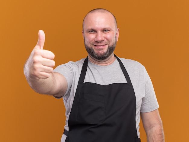 Peluquero masculino de mediana edad sonriente en uniforme que muestra el pulgar hacia arriba aislado en la pared naranja