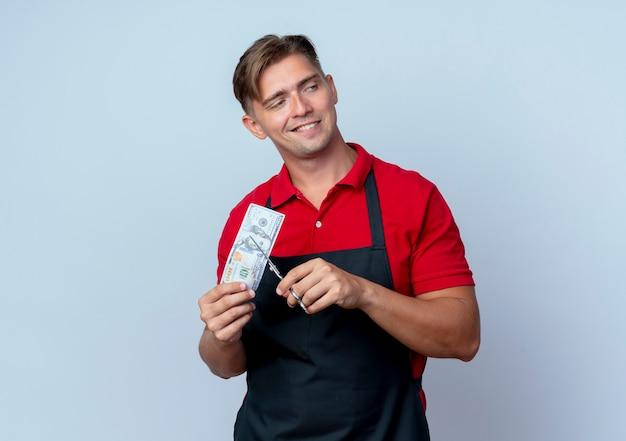 Peluquero masculino rubio confiado joven en uniforme finge cortar el billete de cien dólares mirando al lado aislado en el espacio en blanco con espacio de copia