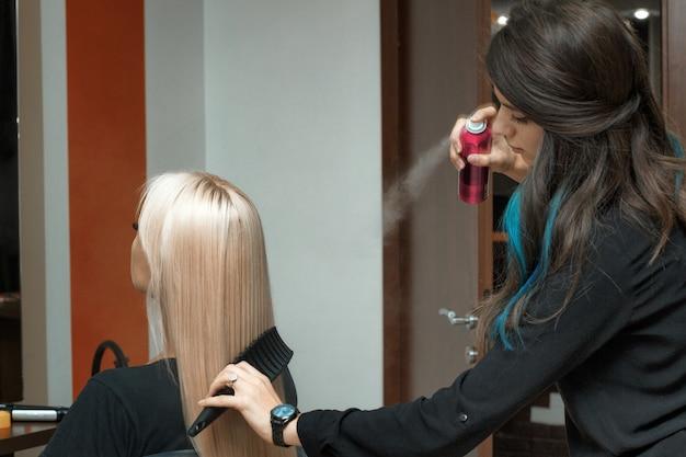 El peluquero peina el cabello largo del cliente.