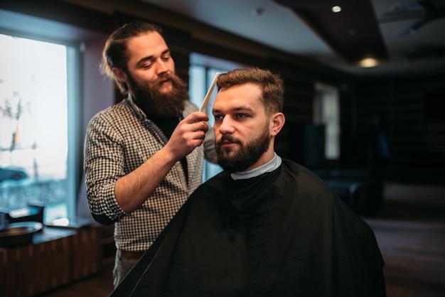 Peluquero peinando el cabello del hombre del cliente en la capa del salón.