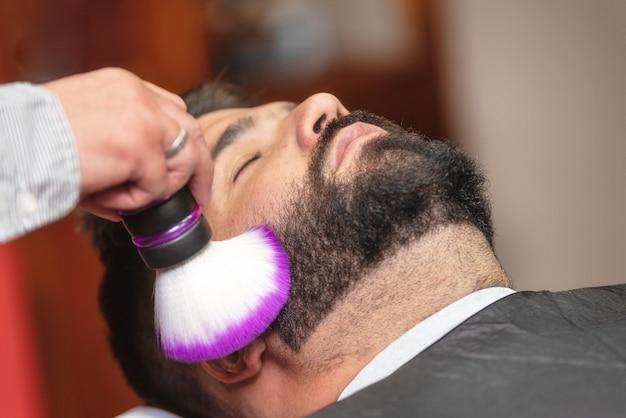 Peluquero del peluquero que limpia la barba con un cepillo en una peluquería.