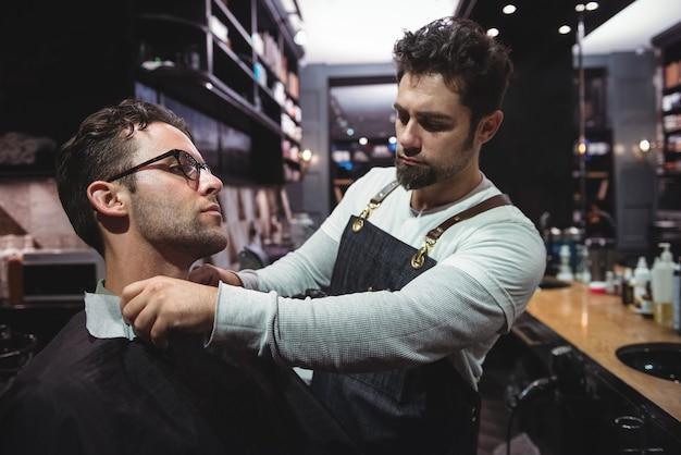 Peluquero poniendo capa sobre el cuello de los clientes