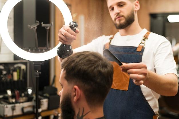 Peluquero preparando el cabello del cliente masculino para cortar