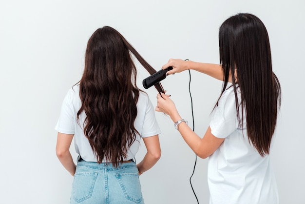 Peluquero profesional alisa el cabello del cliente.
