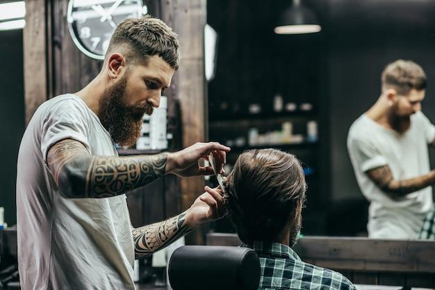 Peluquero profesional con brazos tatuados sosteniendo un peine y haciendo corte de pelo para su cliente