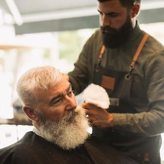 Peluquero profesional con brocha de afeitar y antiguo cliente masculino