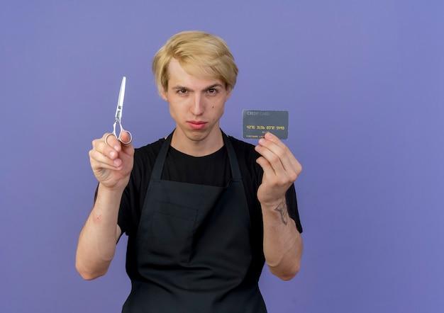 Peluquero profesional en delantal mostrando tarjeta de crédito y tijeras con cara seria