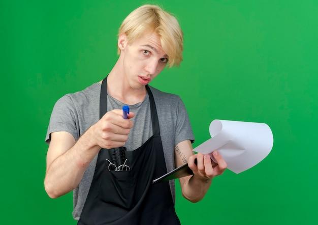 Peluquero profesional en delantal sosteniendo el portapapeles con páginas en blanco y bolígrafo apuntando a la cámara con aspecto de confianza