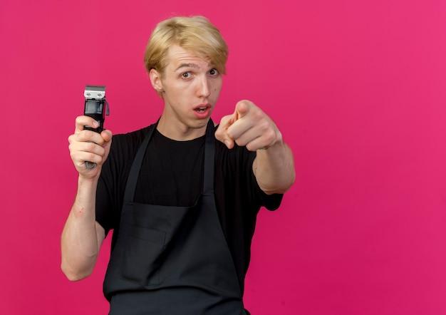 Peluquero profesional en delantal sosteniendo trimmer pointign con el dedo índice a la cámara con expresión escéptica