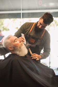 Peluquero profesional con peines y cliente barbudo de edad.
