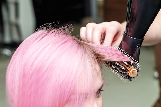 El peluquero profesional está secando el peinado rosado corto.