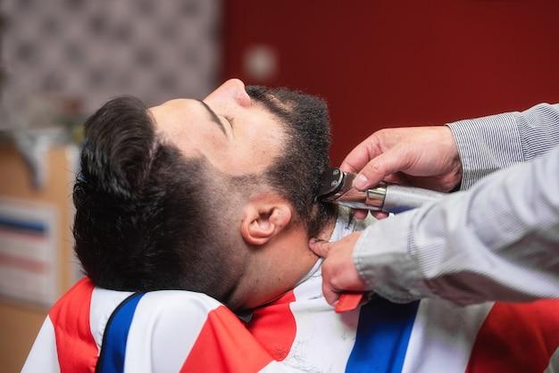 Peluquero que afeita la barba de un hombre barbudo hermoso con una maquinilla de afeitar eléctrica en la peluquería.