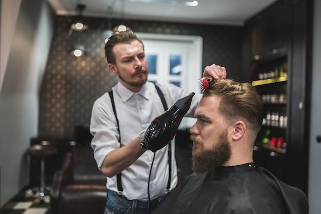 Peluquero que seca el pelo del cliente hermoso