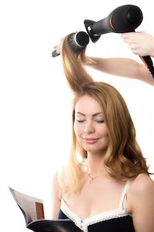 Peluquero rizando el pelo a una mujer